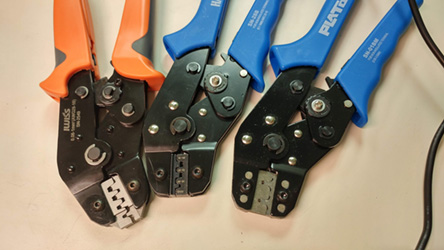 Three of Focus Inc's colorful wire crimping tools sitting side-by-side